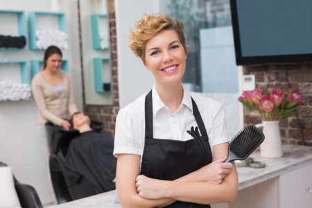 Confident hairdresser smiling at camera at the hair salon photo