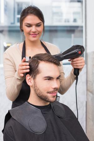 Hair stylist drying mans hair at the hair salon photo