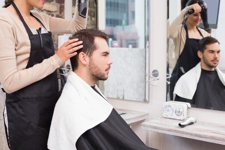 hair stylist: Hair stylist drying mans hair at the hair salon Stock Photo