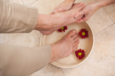 soaking: Pedicurist cleansing customer feet in warm water