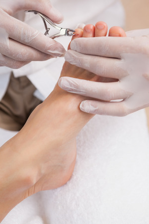 nail clippers: Salon worker using a nail clippers on customers toe nails Stock Photo