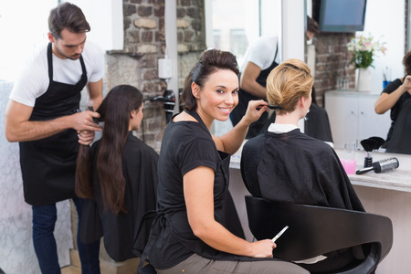 cutting hair: Hairdressers working on their clients at the hair salon Stock Photo