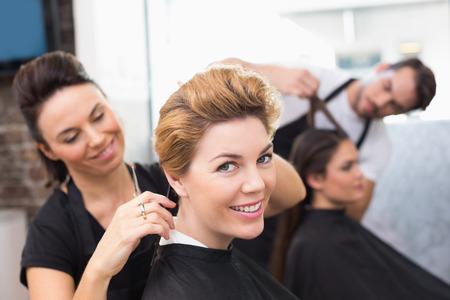Friseure arbeiten an ihre Kunden im Friseursalon Standard-Bild