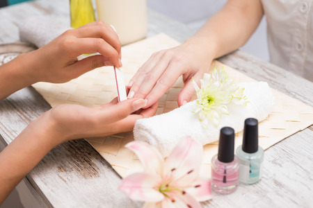 Nail technician giving customer a manicure at the beauty salon Stock Photo