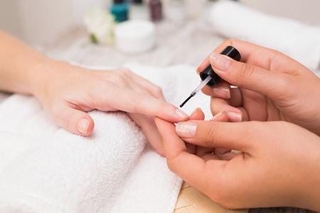 Nail technician giving customer a manicure at the beauty salon photo