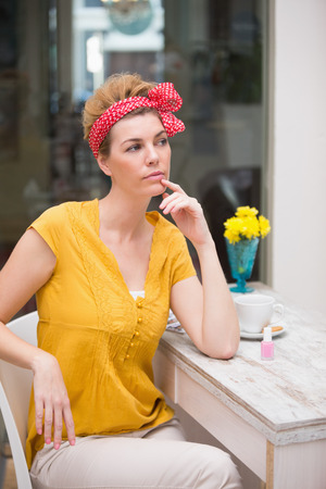 Pretty hipster sitting at table thinking and looking away photo
