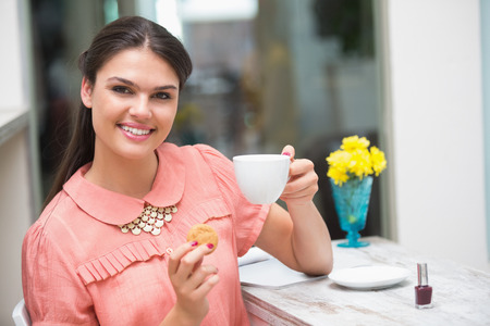 Pretty brunette having a coffee sitting at table photo