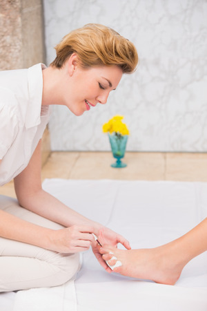 Woman getting a pedicure from beautician at the beauty salon photo