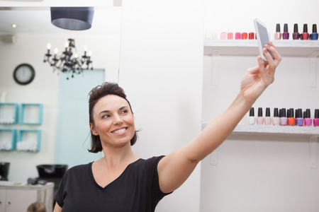 long hair woman: Hairdresser smiling and holding phone taking a selfie Stock Photo