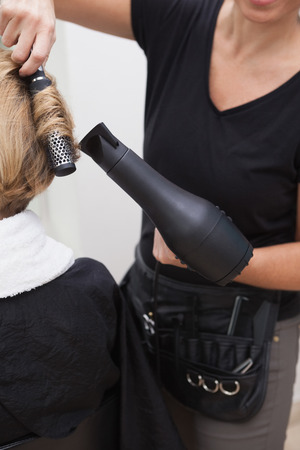 Hairdresser styling customers hair at a salon photo