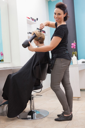 Hairdresser smiling and styling customers hair at a salon photo