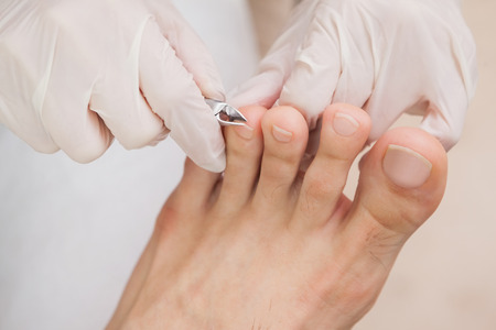 feet relaxing: Customer getting toe nails clipped in a nail salon Stock Photo