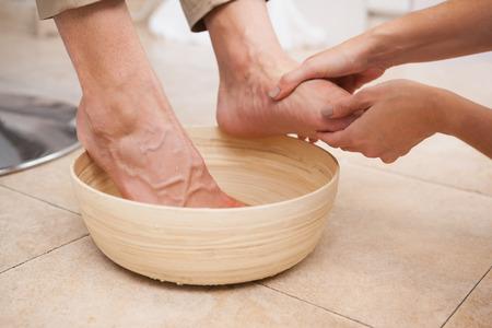 feet washing: Pedicurist cleansing customer feet in warm water