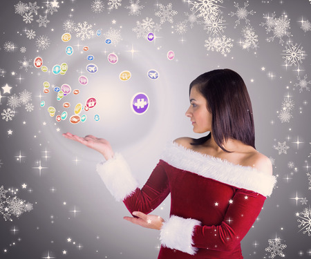 Composite image of Pretty girl presenting in santa outfit  against grey vignette photo