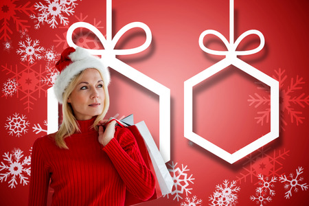 Happy festive blonde with shopping bags against hanging christmas decorations on red photo