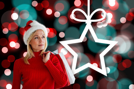 Happy festive blonde with shopping bags against hanging christmas decorations on lights photo