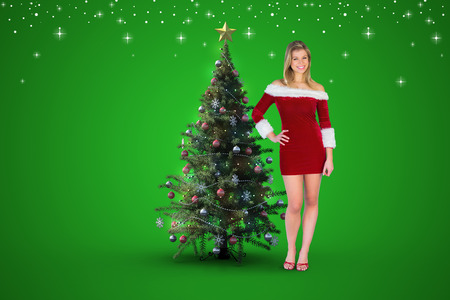 Pretty girl smiling in santa outfit against christmas tree photo