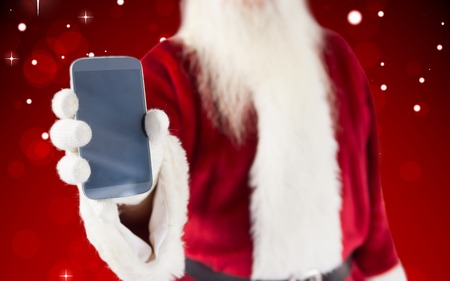 Santa claus showing smartphone against red design with white stars photo