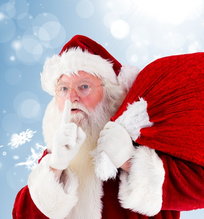 Santa claus carrying sack against blue design with white snowflakes photo