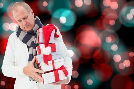 Festive man holding christmas gifts against digitally generated twinkling light design  photo