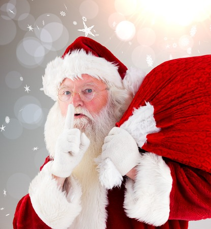 Santa claus carrying sack against grey design with snowflakes photo