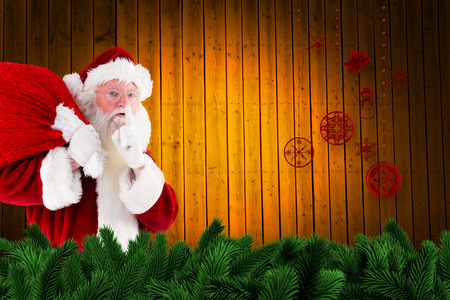 Santa claus carrying sack against fir tree branches and christmas decorations photo