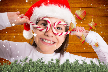 Festive little girl smiling at camera against fir tree branches and christmas decorations photo