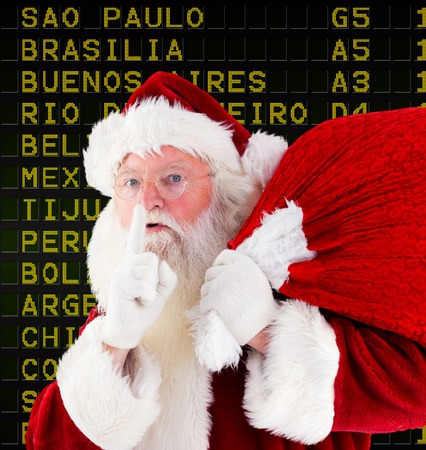 Santa claus carrying sack against black airport departures board for south america photo