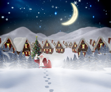 Santa walking in the snow against cute christmas village at night photo