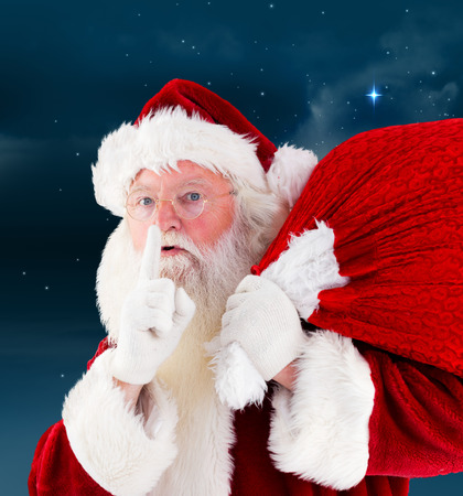 Santa claus carrying sack against stars twinkling in night sky photo