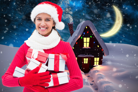 Festive brunette holding gifts against christmas house photo