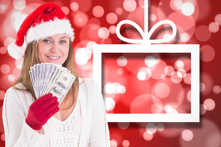 Festive blonde showing fan of dollars against hanging christmas decorations on red photo
