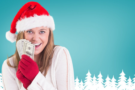 Festive blonde showing fan of dollars against fir tree forest silhouette over blue photo