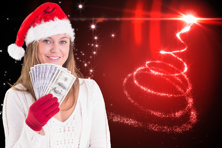 Festive blonde showing fan of dollars against christmas tree spiral of light photo