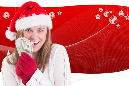 Festive blonde showing fan of dollars against fir trees with snow flakes photo