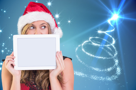 Festive blonde showing a tablet against christmas tree spiral of light photo