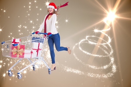 Festive blonde pushing trolley full of gifts against christmas tree spiral of light photo