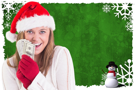 Festive blonde showing fan of dollars against christmas themed snow flake frame photo