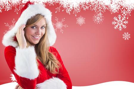 pere noel sexy: Festive blonds souriant � la cam�ra contre la silhouette de sapin plus rouge Banque d'images