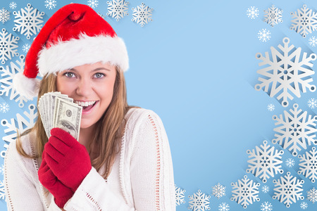 Festive blonde showing fan of dollars against snow flake frame design on blue photo