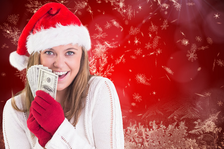 Festive blonde showing fan of dollars against red snow flake pattern design photo