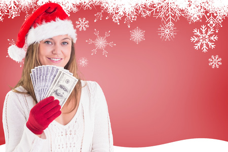 Festive blonde showing fan of dollars against fir tree silhouette over red photo