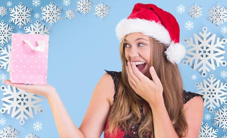 Festive blonde holding a gift bag against snow flake frame design on blue photo