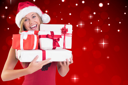 Festive blonde holding pile of gifts against red design with white stars photo