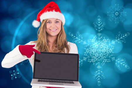 Festive blonde pointing to laptop against blue snow flake pattern design photo