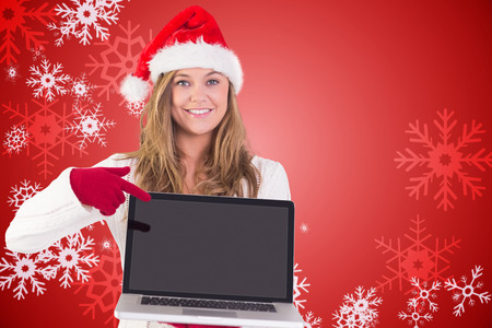 Festive blonde pointing to laptop against red snow flake pattern design photo