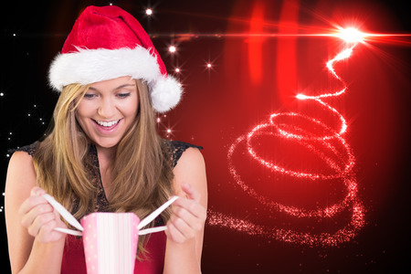 Festive blonde opening a gift bag against christmas tree spiral of light photo