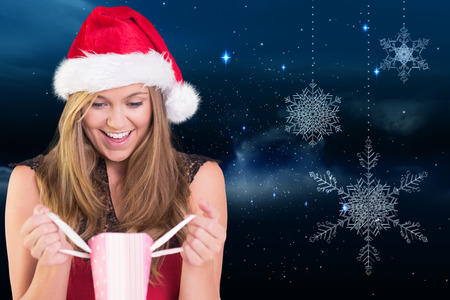 Festive blonde opening a gift bag against snowflakes hanging against starry sky photo
