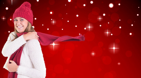 Happy blonde in winter clothes against red design with white stars photo