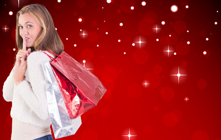 Pretty blonde keeping a secret holding bags against red design with white stars photo